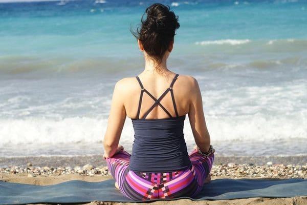 Девушка медитирует у моря