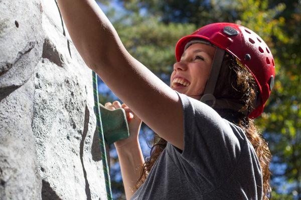 Девушка карабкается на скалу