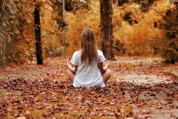 Девушка медитирует в лесу