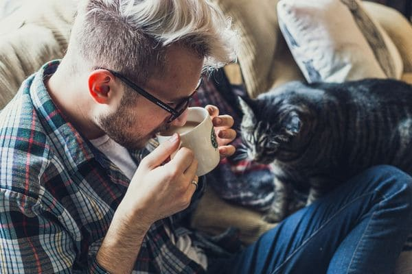 Мужчина с кофе и котом